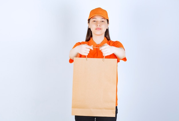 Female service agent in orange color uniform holding a shopping bag and presenting it to the customer.