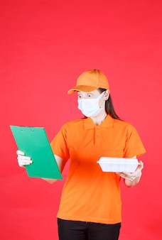 Female service agent in orange color uniform and mask holding a takeaway food package and checking the green folder.