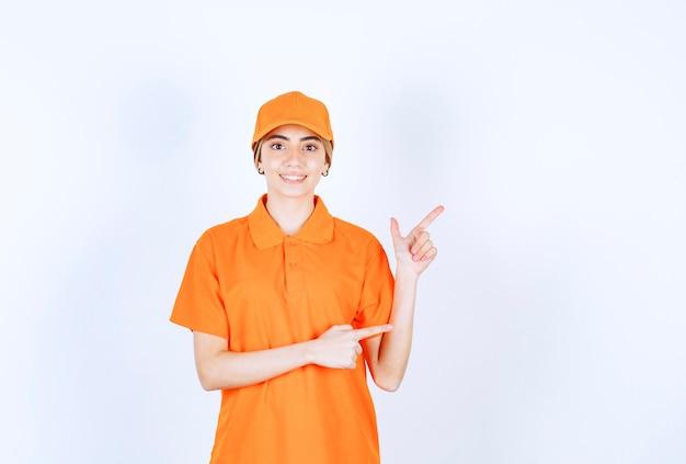 Agente di servizio femminile in uniforme arancione che indica qualcosa da parte