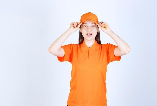 Женщина-агент службы в оранжевом дресс-коде проверяет головной убор