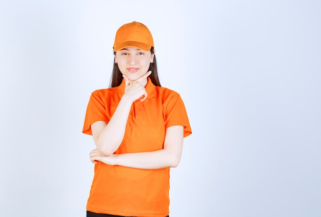 Агент женской службы в оранжевом дресс-коде выглядит задумчиво
