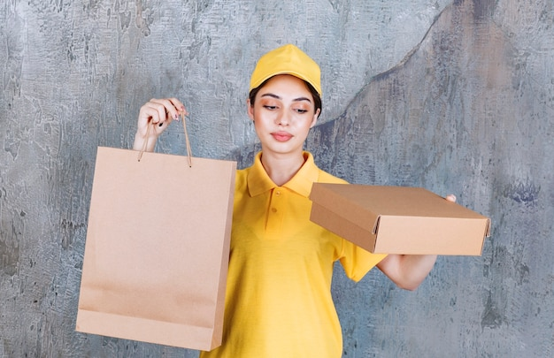 Female service agent in yellow uniform holding a cardboard box and paper bag.
