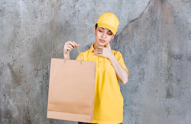 Female service agent in yellow uniform holding a paper bag and looks confused.