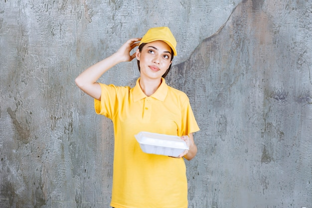 Female service agent in yellow uniform holding a plastic takeaway box and looks confused and thoughtful.