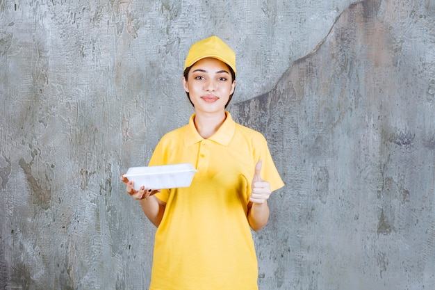 Female service agent in yellow uniform holding a plastic takeaway box and showing positive hand sign.