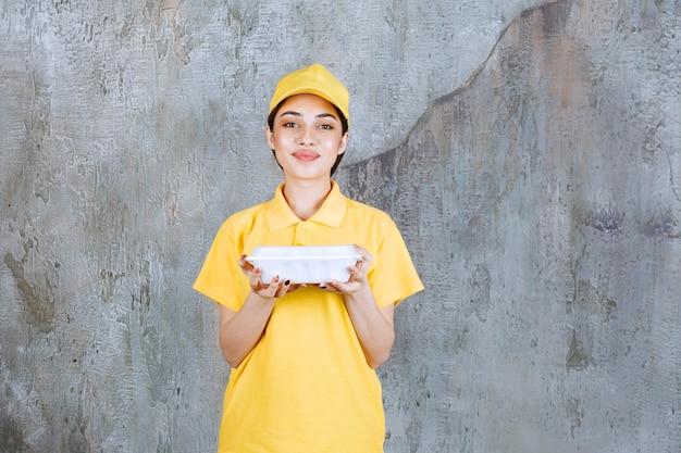 Agente di servizio femminile in uniforme gialla con in mano una scatola di plastica da asporto