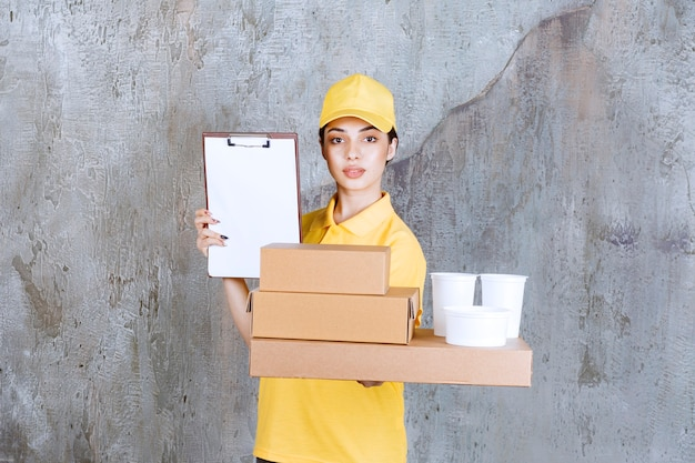 Female service agent in yellow uniform holding a stock of takeaway cardboard boxes and plastic cups and asking for a signature.