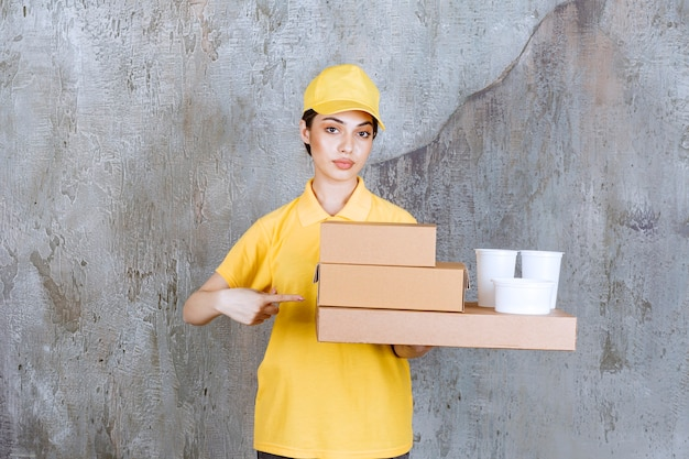 Female service agent in yellow uniform holding a stock of takeaway cardboard boxes and plastic cups