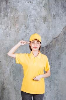 L'agente di servizio femminile in uniforme gialla che sta sul muro di cemento sembra premuroso.