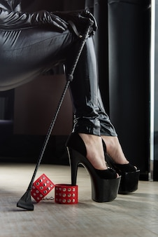 Female sexy legs with handcuffs and crop whip