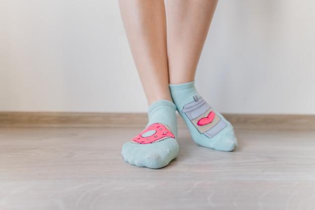 Female sexy naked legs standing on wooden floor in front of white wall. women`s feet in short socks.