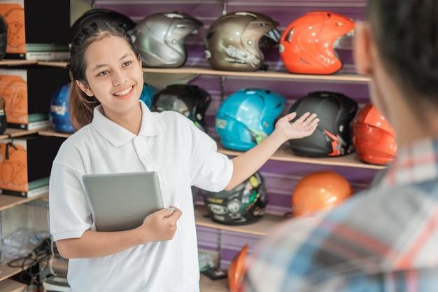 タブレットを手振りで握っている女性の店員が、ヘルメットショップで男性の消費者にヘルメットを提供しました