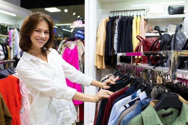 Female shop assistant in white shirt helps to buy clothing in shirt department