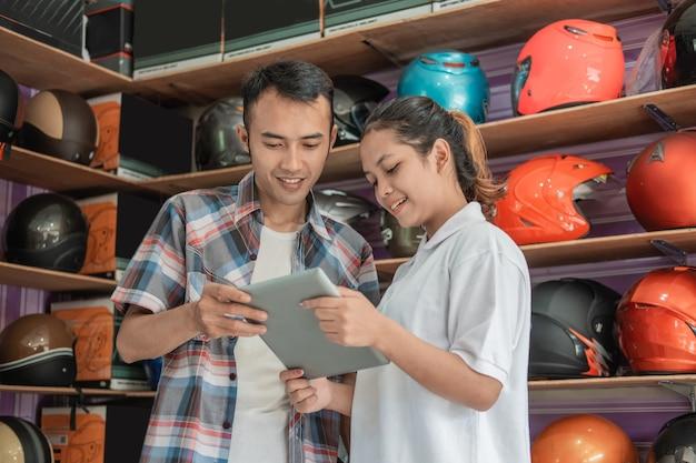 女性の店員がヘルメット店で男性にタブレットを使ったオンラインショップを宣伝