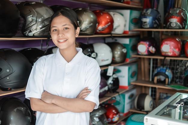 ヘルメットショップで手を組んで立っている女性の店員