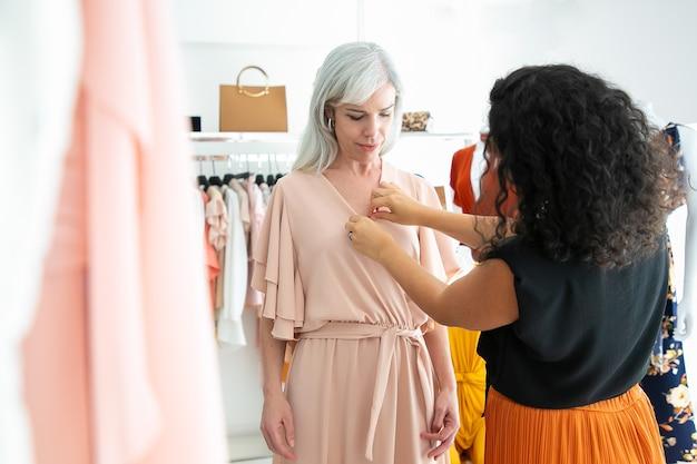 Venditore femminile del negozio che aiuta il cliente a provare il nuovo vestito. donna che sceglie i vestiti nel negozio di moda. acquisto di vestiti nel concetto di boutique