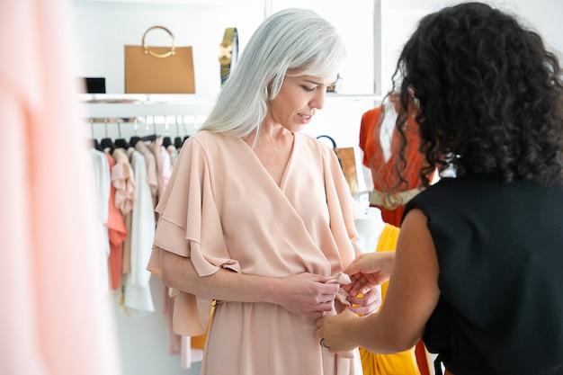 Venditore femminile del negozio che aiuta la donna a provare il nuovo vestito e legare la cintura. cliente che sceglie i vestiti nel negozio di moda. acquisto di vestiti nel concetto di boutique