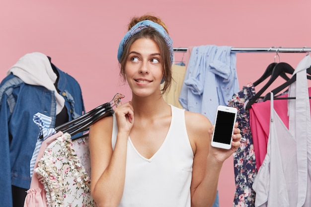 부티크에 서있는 여성 쇼핑 중독자, 시도를위한 옷이 많은 옷걸이를 가져 가거나, 꿈꾸는 표정으로 따로보고, 가져갈 것을 결정하고, 다른 손에 현대 휴대 전화를 유지