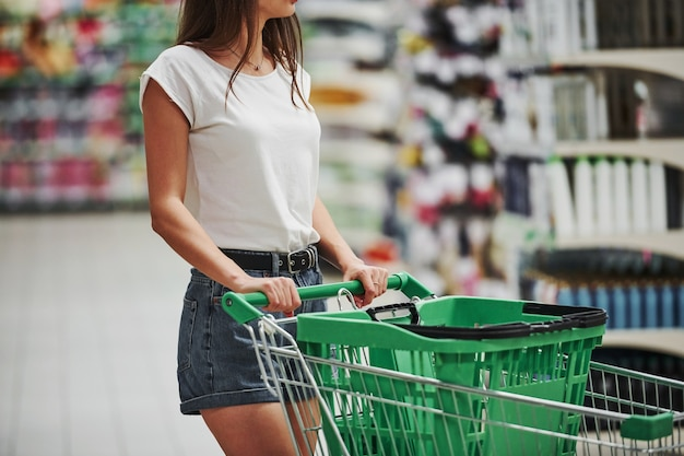 Female shopper in casual clothes in market looking for products.
