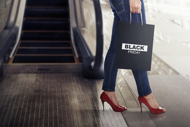 Female shopper with black friday paper bag