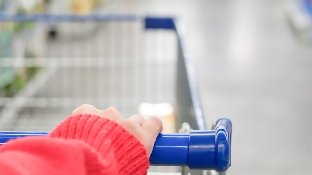 Female shopper with trolley blurred motion of supermarket department store