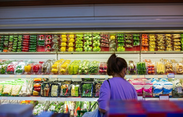 健康のためにスーパーマーケットで買い物をする女性は、スーパーマーケットの食べ物に野菜や果物を置いています。
