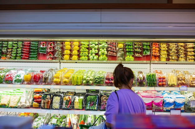 Female shopping in the supermarket for health a shopping shelf vegetable and fruit put on at food in the supermarket.