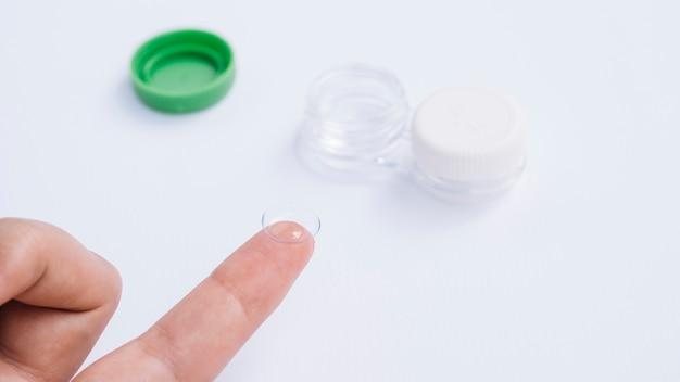 그의 손가락에 콘택트 렌즈를 보여주는 여성