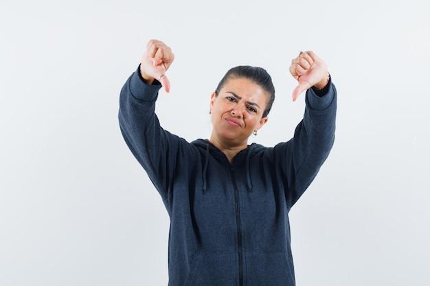 Femmina che mostra i doppi pollici in giù in felpa con cappuccio e sembra delusa. vista frontale.