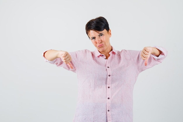 Female showing double thumbs down in pink shirt and looking discontent. front view.