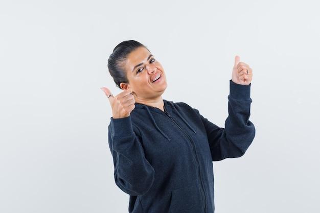 Femmina che mostra il doppio pollice in alto in felpa con cappuccio e sembra allegra. vista frontale.
