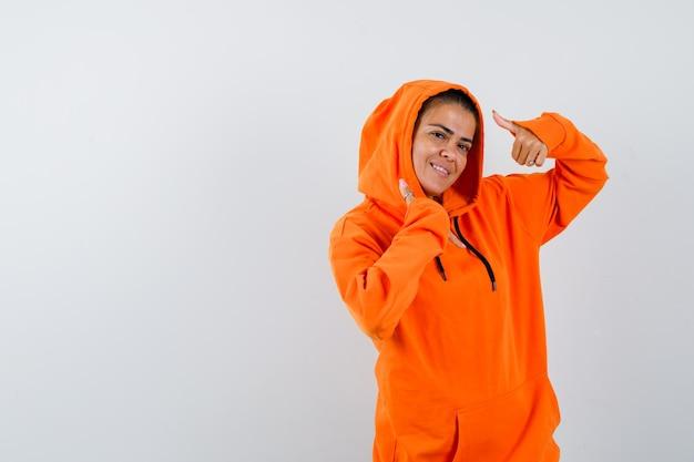 オレンジ色のパーカーで二重の親指を見せて幸せそうに見える女性