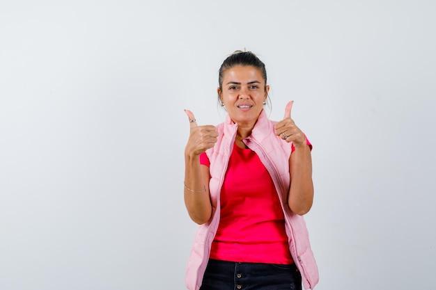 Tシャツ、ベストで二重の親指を示し、自信を持って見える女性