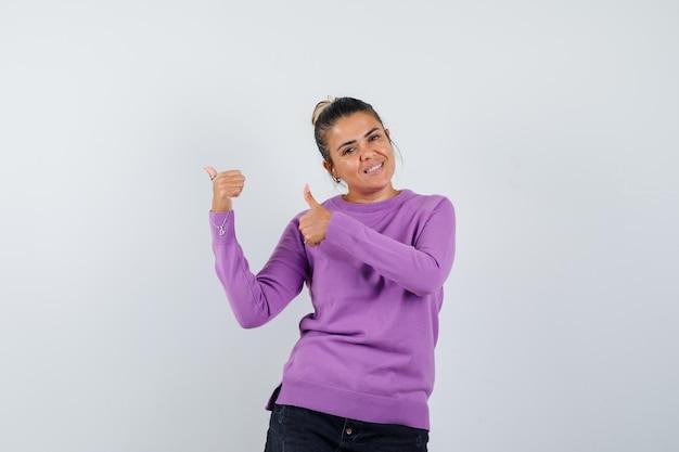 ウールのブラウスで二重の親指を示し、自信を持って見える女性