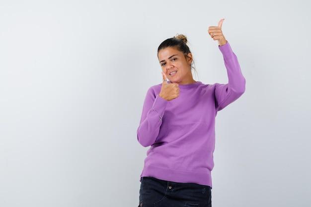 ウールのブラウスで二重の親指を見せて幸せそうに見える女性