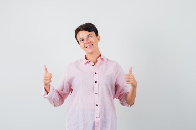 Femmina che mostra i doppi pollici in su in camicia rosa e che sembra felice, vista frontale.