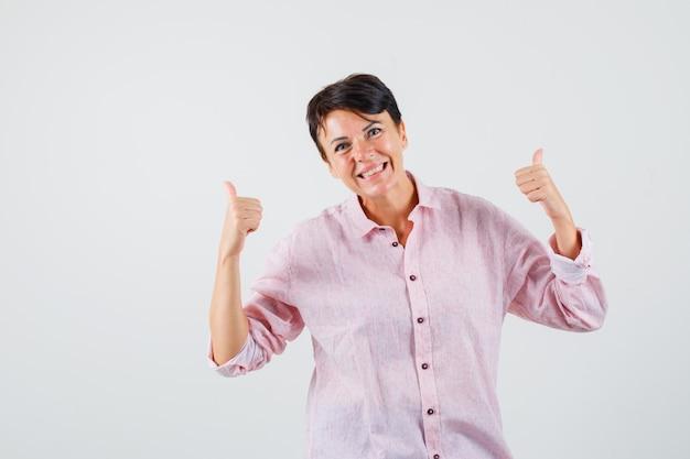 Femmina che mostra i doppi pollici in su in camicia rosa e sembra allegra. vista frontale.