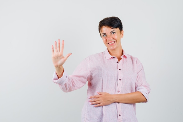 ピンクのシャツを着て5本の指を示し、陽気に見える女性、正面図。