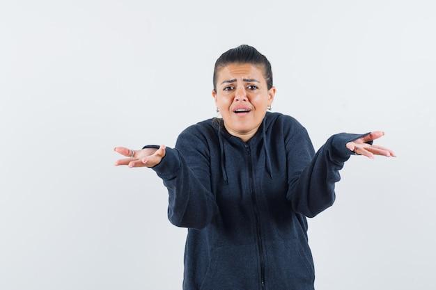 パーカーで無力なジェスチャーを示し、混乱しているように見える女性。正面図。