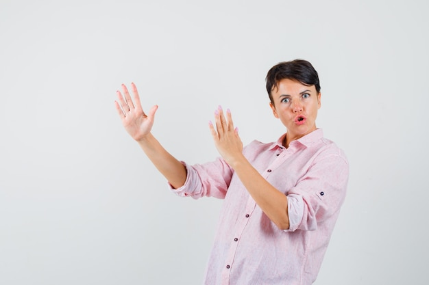 Female showing karate chop gesture in pink shirt and looking powerful. front view.