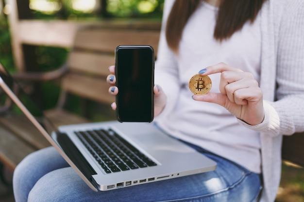 공간을 복사하기 위해 빈 화면이 있는 카메라 휴대전화에 여성이 표시됩니다. 야외에서 비트코인, 현대적인 노트북 pc 컴퓨터를 들고 벤치에 앉아 있는 여자. 모바일 오피스, 온라인 가상 화폐 개념.