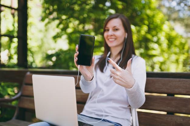 공간을 복사하기 위해 빈 화면이 있는 카메라 휴대전화에 여성이 표시됩니다. 야외 거리에서 현대 노트북 pc 컴퓨터 작업을 하는 벤치에 앉아 있는 여자. 모바일 오피스. 프리랜서 비즈니스 개념입니다.