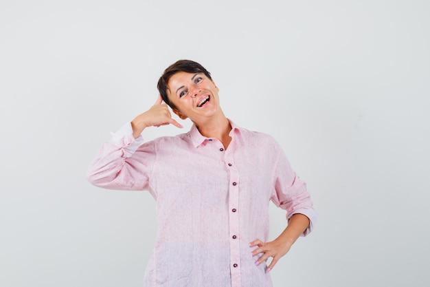여성 분홍색 셔츠에 전화 제스처를 표시 하 고 쾌활 한, 전면보기를 찾고.
