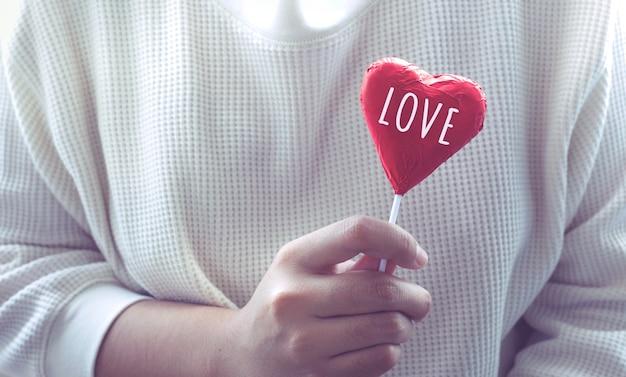 심장 모양에 레드 초콜릿을 보여주는 여성.