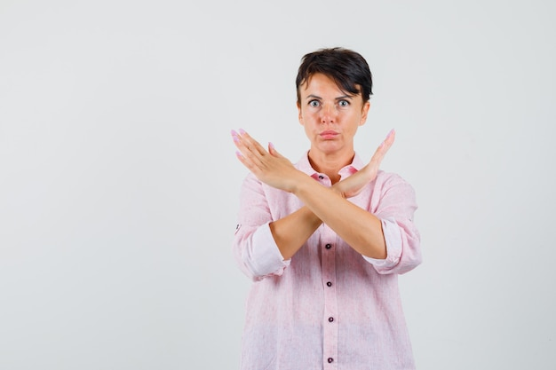 Female showing refusal gesture in pink shirt and looking anxious. front view.