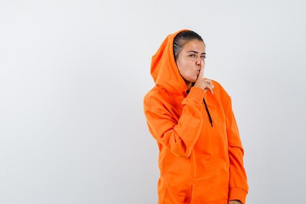 オレンジ色のパーカーで沈黙のジェスチャーを示し、魅力的に見える女性