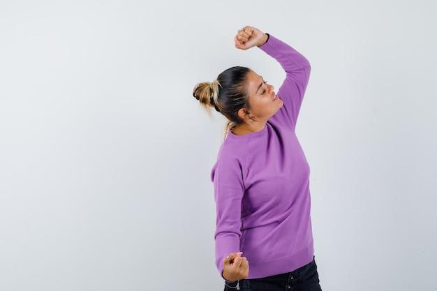 ウールのブラウスで勝者のジェスチャーを示し、至福に見える女性