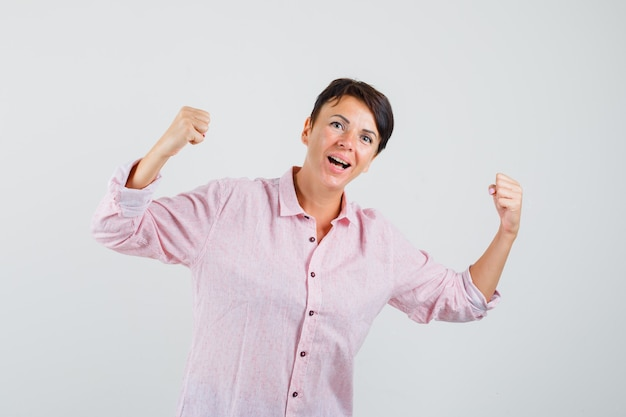 Femmina che mostra il gesto del vincitore in camicia rosa e che sembra felice. vista frontale.