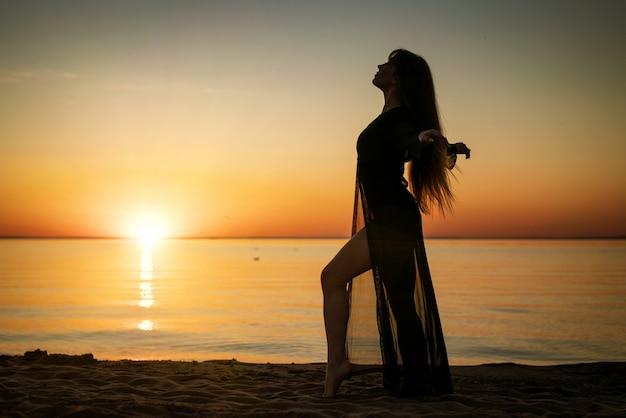 海と空を背景に日没時の女性のシルエット