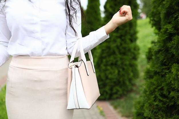 Женский силуэт в светлой одежде держит сумку на согнутой руке